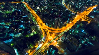Aerial view time-lapse of a massive highway intersection at night in Tokyo