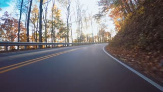 Autumn POV driving shot of the Blue Ridge Parkway through North Carolina at sunset