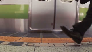 Business men walk on the subway platform in slow motion