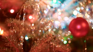 Christmas tree with bright red ornament gradually comes into focus