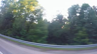 Driving on the highway with sunlight through the trees