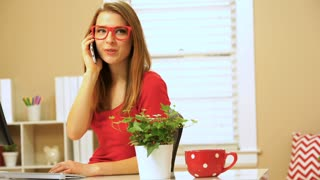 Happy young woman speaking on the phone in her office