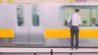 Man standing on the train station platform as train goes by