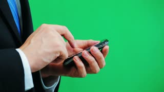 Man using a cellphone isolated on green screen background