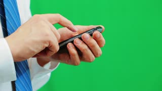 Man using a cellphone isolated on green screen