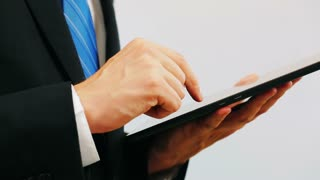 Man wearing a suit using a tablet computer