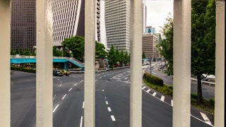 Moving time-lapse through the railing bars with traffic and skyscrapers