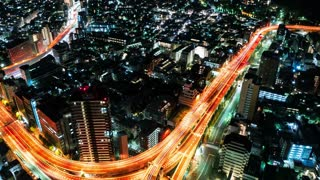 Night turns to day over a massive highway intersection in Tokyo, Japan