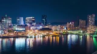 Panning time lapse of ships entering colorful Kobe harbor at night. Kobe, Japan.