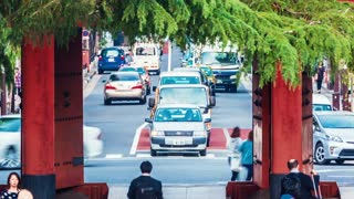 People and cars pass by the gateTokyo of a temple in the
