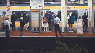 People boarding and exiting trains at a subway station in Tokyo