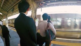 People wait at the Kyoto Station platform, Kyoto, Japan.