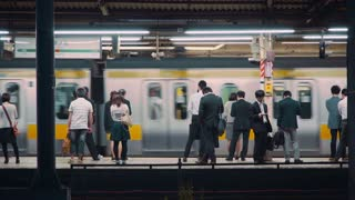 People waiting to board trains at the subway station in Tokyo at night