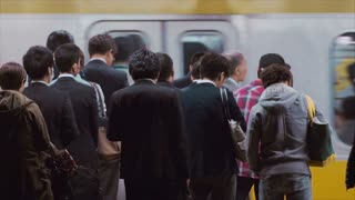 People waiting to board trains at the subway station in Tokyo in slow motion