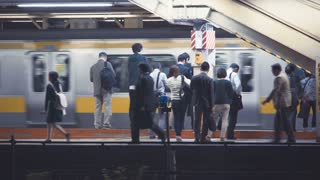 People waiting to board trains at the subway station in Tokyo