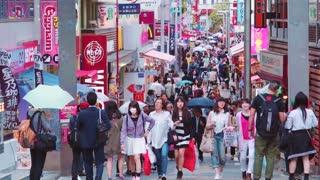People walk and shop along Takeshita Street in Harajuku, Tokyo, Japan