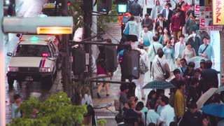 People walk down the street outside Shinjuku station in the rain