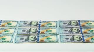 Piggy bank marching across 100 dollar bills