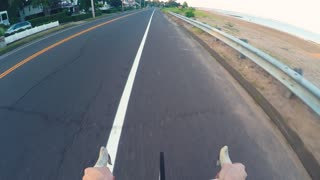 POV video of person riding a bicycle along the coastline