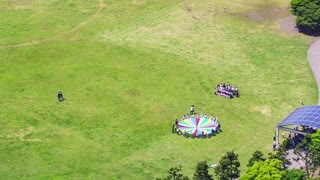 Time-lapse of a large group of children playing in a field