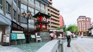 Timelapse at the clock tower in downtown Matsuyama Japan, with tourists watching