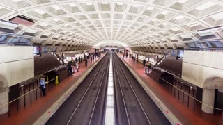 Trains and passengers travel through a Washington Metro Station