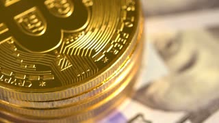 Bitcoin coins rotating on a pile of 100 dollar bills