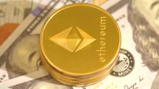 Ethereum ether cryptocurrency coins rotating on a pile of 100 dollar bills