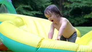 Happy toddler playing in his backyard pool in slow motion