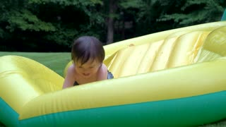 Happy toddler playing in his backyard pool