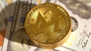 Monero cryptocurrency coins rotating on a pile of 100 dollar bills
