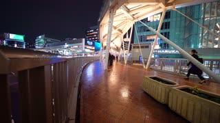 OSAKA – OCTOBER 16 2017: People walk through Osaka, Japan at night in the rain