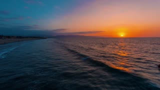 Sunrise time-lapse of Venice Beach, California with surfers and swimmers