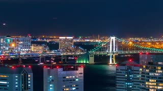 Sunset time-lapse of Tokyo Bay with a view of the Rainbow Bridge and planes and boats