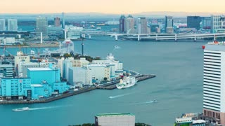 Sunset time-lapse of Tokyo Bay with a view of the Rainbow Bridge with planes and boats