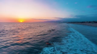 Sunset time-lapse of Venice Beach, California with surfers and swimmers