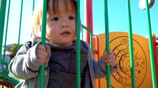 Toddler boy playing on the playground outside