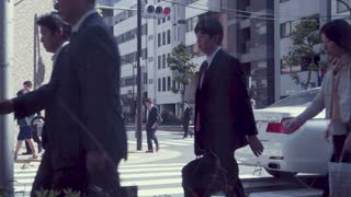 TOKYO, JAPAN - JUNE 23, 2015: People cross the street in a business district of Tokyo, Japan in slow motion