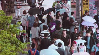 TOKYO - JUNE 7 2015: People walk down the street outside Shinjuku Station, Shinjuku, Tokyo, Japan in the night rain