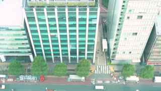 Tokyo office building with traffic reflected on its facade
