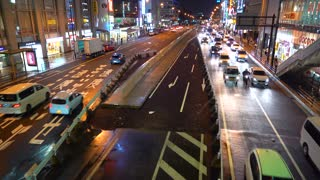 Traffic passes through a busy intersection in Osaka, Japan on a rainy night