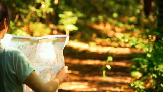 Woman reading a map on a forest trail in slow motion