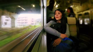 Woman traveling by train looking out the window