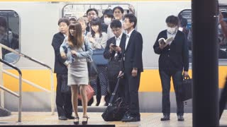 Woman waiting to board a train at the subway station in Tokyo