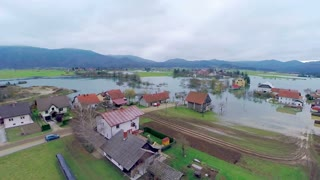 Above flooded homes on a cloudy day. Wide aerial shot of houses in water after flooding river far away. Very depressed scene.