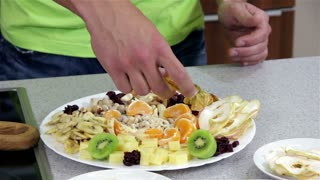 Adding Honey to Healthy Dish with Seeds. Preparing dish with healthy diet food from seeds, dried fruit and some cheese. Professional cooking recipe.