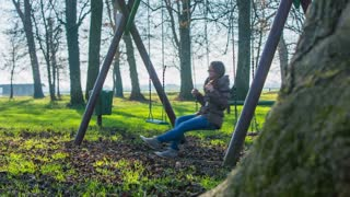 Adult girl swinging in playground. Attractive young woman in warm clothes enjoying swinging in kids playground park.