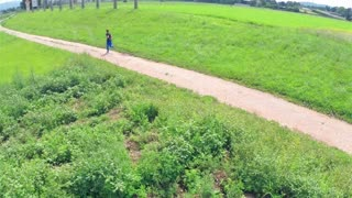 Aerial Fisheye Runner on Track in Nature. Running to success. Aerial shot on green field with great landscape.