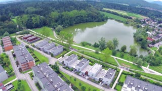 Aerial flight over settlement around small lake. Small lake near suburban apartments, with park and dock. Flying over.