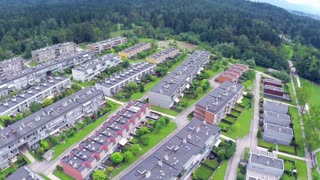 Aerial of large apartment complex by the river. Aerial fly over settlement buildings placed in rows. Big neighborhood.